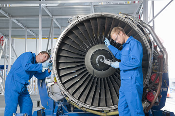 Engineers inspecting engine of passenger jet in hangar