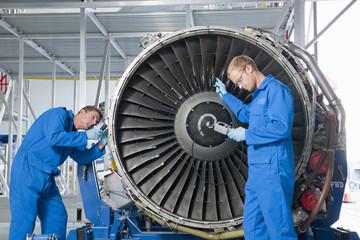 Engineers inspecting engine of passenger jet in hangar