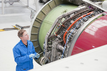 Engineer inspecting engine on passenger jet in hangar