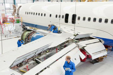 Engineers assembling passenger jet in hangar