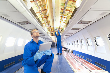 Engineer with tablet looking at wiring in passenger jet