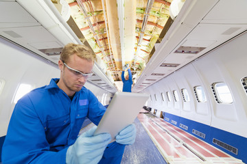 Engineer with digital tablet inside passenger jet