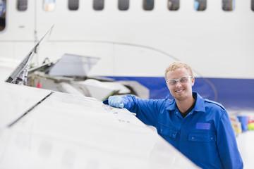 Smiling engineer leaning on wing of passenger jet in hangar