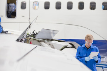 Engineer with tablet next to passenger jet in hangar