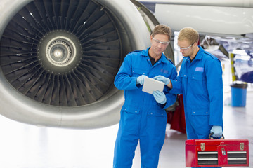 Engineers using digital tablet next to jet engine in hangar