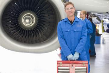 Engineer holding tool box next to jet engine in hangar