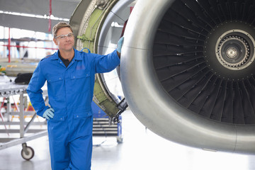 Engineer next to engine of passenger jet in hangar