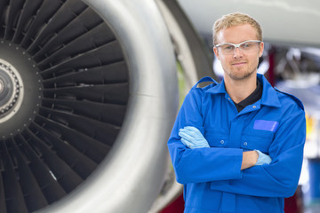Portrait of engineer next to engine of passenger jet in hangar
