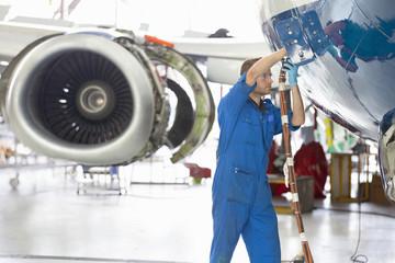 Engineer assembling passenger jet in hangar