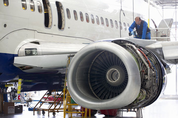 Engineer drilling into wing of passenger jet in hangar