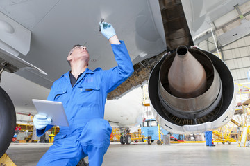Engineer inspecting underside of wing on passenger jet in hangar