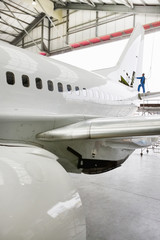 Engineer assembling tail of passenger jet in hangar
