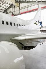 Engineer assembling tail of passenger jet in hangar