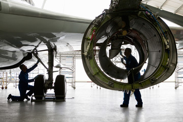 Engineer inspecting engine casing on passenger jet in hangar