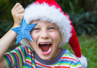 Surprised cute child in Santa hat holding sparkling blue star
