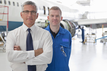Businessman and engineer in front of passenger jet in hangar