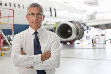 Businessman in front of passenger jet in hangar