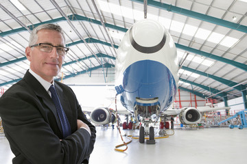 Portrait of confident businessman near passenger jet in hangar