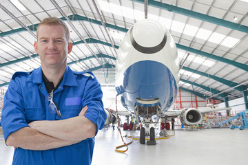 Engineer near passenger jet in hangar