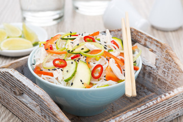 Thai salad with vegetables, rice noodles and chicken in a bowl