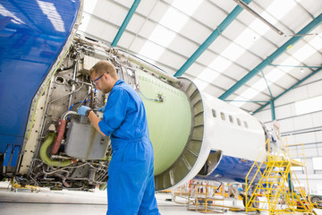 Engineer assembling engine on passenger jet in hangar