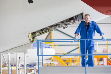 Engineer on platform near passenger jet in hangar