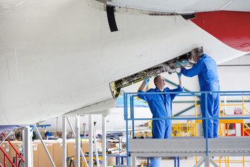 Engineers repairing passenger jet in hangar
