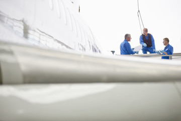 Engineers talking at wing of passenger jet in hangar