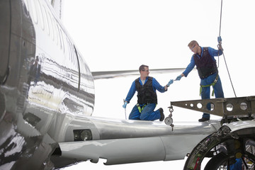 Engineers repairing wing on passenger jet in hangar