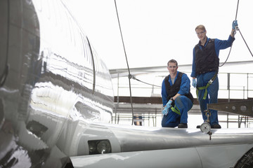 Engineers on wing of passenger jet in hangar