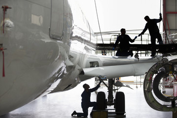 Engineers repairing wing of passenger jet in hangar