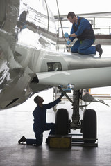 Engineers repairing landing gear on passenger jet in hangar