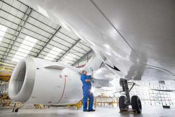 Engineer inspecting engine of passenger jet in hangar