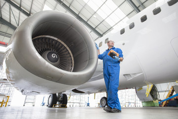 Engineer next to engine of passenger jet in hangar