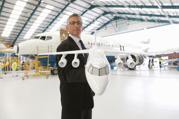 Businessman holding model airplane with passenger jet in hangar
