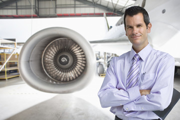 Businessman near passenger jet in hangar