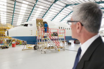 Businessman watching engineer next to passenger jet in hangar