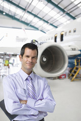 Businessman standing near passenger jet in hangar