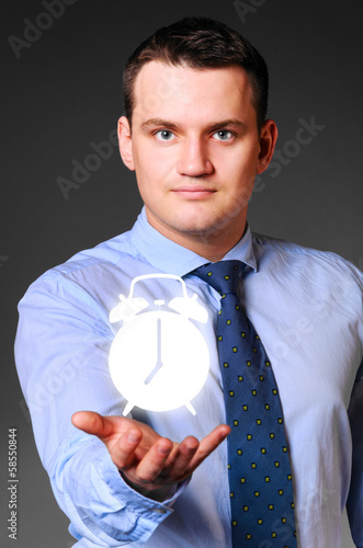 businessman is holding alarm clock