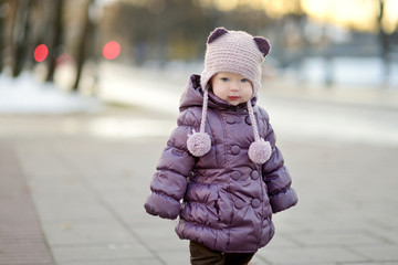 Toddler girl having fun on winter day in a city