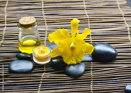 Zen rock with candle, massage oil, stones on mat