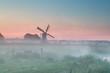 Dutch windmill in summer morning fog