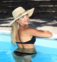 portrait the smart blonde in a hat in swimming pool