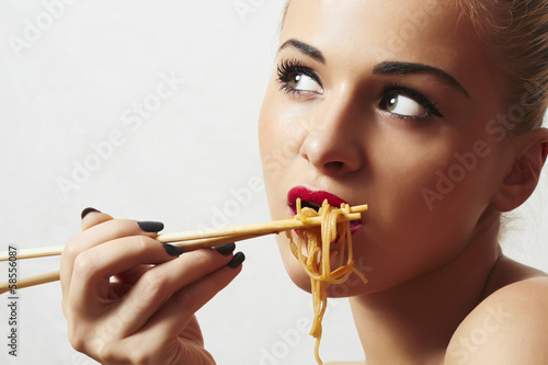 Beautiful woman eating chinese food. wok. noodles