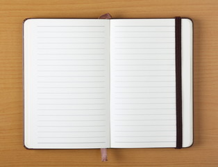 Empty lined paper notebook on a wood background