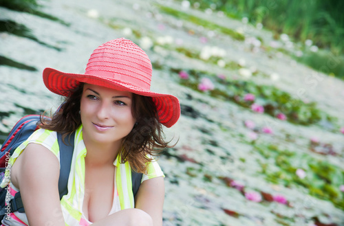 Beautiful woman in a hat and lake with water lilies