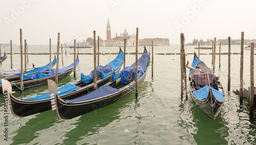 Gondolas with main blue color moored in the channel