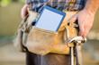 Digital Tablet And Hammer In Carpenter's Tool Belt