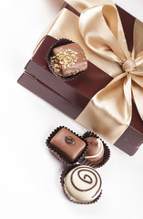 brown box with candies and golden tape isolated on the white