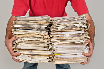 Man with a bunch of old newspapers in the hands